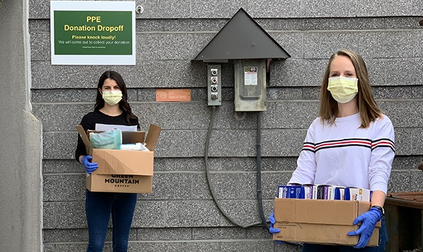 Woman wearing  face masks and gloves carrying boxes of PPE to donate