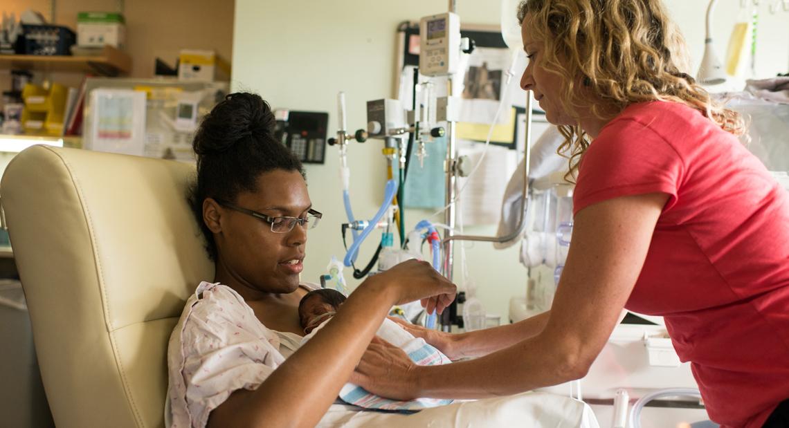 Provider handing patient her baby