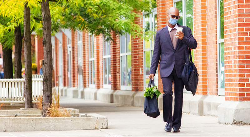 Man wearing a mask walking while checking phone and carrying groceries