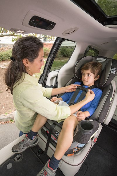 Adult buckles young child into car seat that is forward-facing