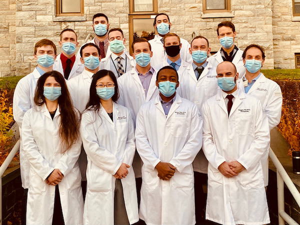 Photo of 15 Orthopaedic Surgery residents wearing masks looking straight at the camera. They are all wearing white coats and face masks.