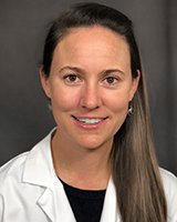 Headshot of a young female physician. Dr. Anderson has long straight brown hair. Dr. Anderson is wearing a black crew shirt under white coat. She is sitting in front of a light grey background.