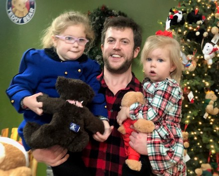 Man holding his two toddler girls posing in front of a Christmas tree.