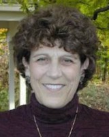 Headshot of UVMHN trustee Allie Stickne. She is wearing a dark purple turtle neck and a thin necklace. She has short curly hair.