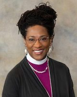 Headshot of Bishop Macvean Brown. She is sitting against a grey background. She is wearing a black sweater over a bright purple shirt. She is wearing glasses and her braided hair in a bun on her head.