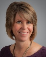 Headshot of UVMHN trustee, Geena Giltz Mccullough, sitting against a grey background. She has short blond hair and it wearing a necklace and purple blouse.