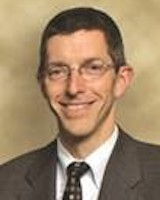 Headshot of UVMHN trustee John Dwyer. He is smiling at the camera posing in front of a light brown background. The gentleman is wearing glasses, a white collard shirt and dark brown tie under a brown suit jacket.