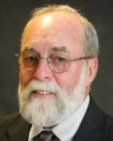 Headshot of trustee Kevin hart. He is an older gentleman smiling at the camera. He is wearing glasses, a white collared shirt and black suit jacket.