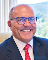 Headshot of UVMHN trustee Michael Dellipriscoli. He is smiling at the camera and wearing glasses, a blue suit, white collard shirt and red tie.
