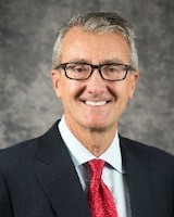 Headshot of trustee Richard Page. He is smiling at the camera, posing in front of a grey background. He wearing a white collared shirt and navy suit jacket. He has short grey hair and is wear black glasses.