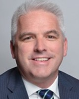 Headshot of trustee Tom Golonka. He is smiling at the camera, wearing a white collared shirt and navy suit jacket.