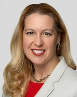 Headshot of UVMHN trustee Victoria Duley. She is posing for the camera in front of a white background. She has long blond hair and is wearing a red blouse under a white suit jacket.