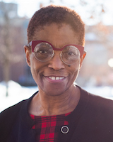 Headshot of UVMMC Board Trustee, Noma Anderson, standing outside the medical center. She is wearing a red and black check blouse and a black cardigan. She is wearing red glasses.