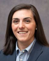 Headshot photo of young female resident physician posing against a grey background. She is wearing a grey suit coat over a light blue collared short.