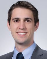 Headshot photo of young resident physician posing against a light grey background. He is wearing a grey suit coat over a light blue collared shirt.
