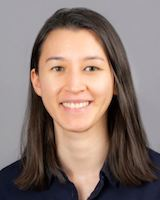 Headshot photo of young female resident physician posing against a grey background. She is wearing a black collared short.