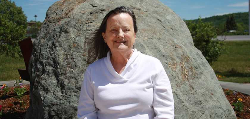 Portrait of Linda sitting outside in the sun in front of a large boulder. She is in her 50's, has brown shoulder length hair and wearing a white sweater.
