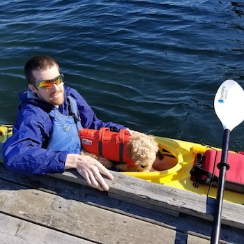 Photo of Marc Hammond sitting in a kayak with his small dog.