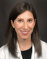 Headshot of Barnara Decker, MD, sitting against a grey background. She has medium length dark brown hair and is wearing her white coat.