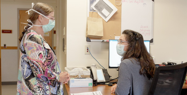 A masked provider standing at the desk of the Hospice & Palliative Care administrative assistant.