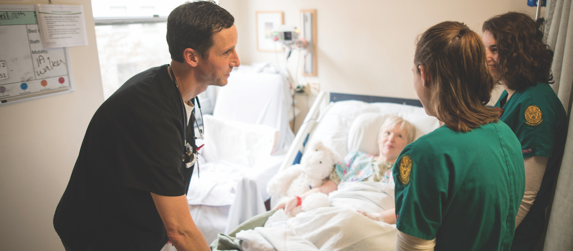 Three CNHS nurses on rounds visiting a elderly patient.