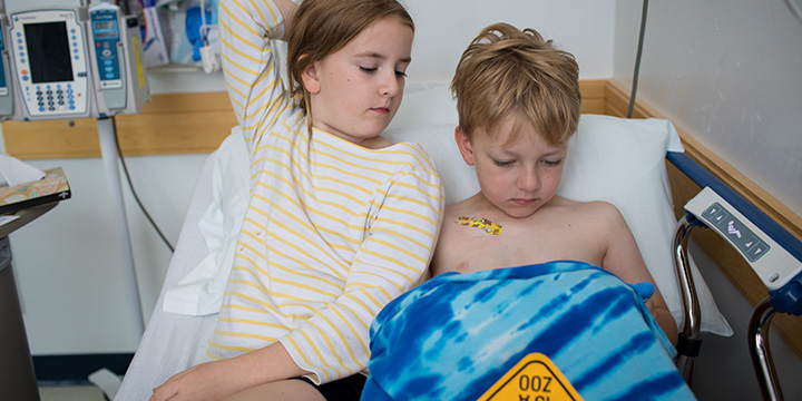 Two children laying in a hospital bed together