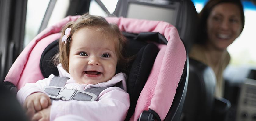 Toddler girl smiling from car seat