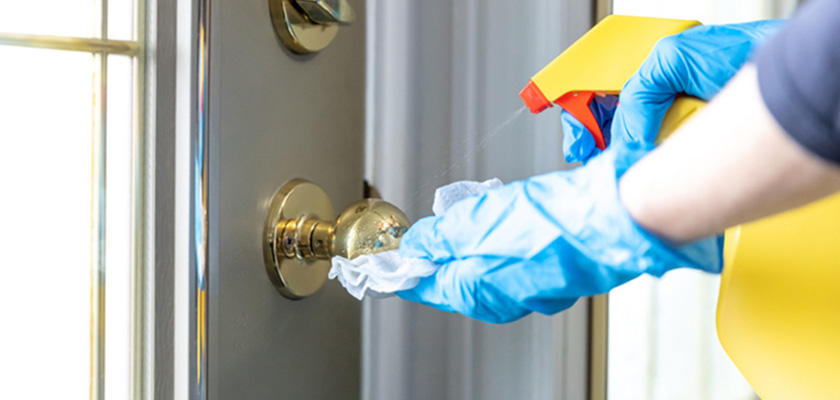 Gloved hand spraying doorknob with cleaner