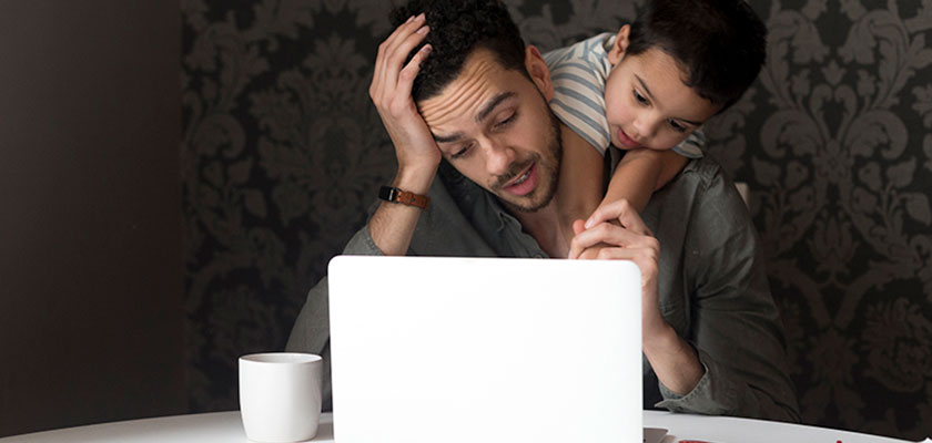 Dad working on laptop with son draped on shoulders
