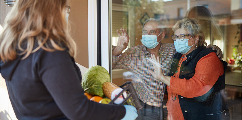 Older couple wearing masks accepting grocery delivery