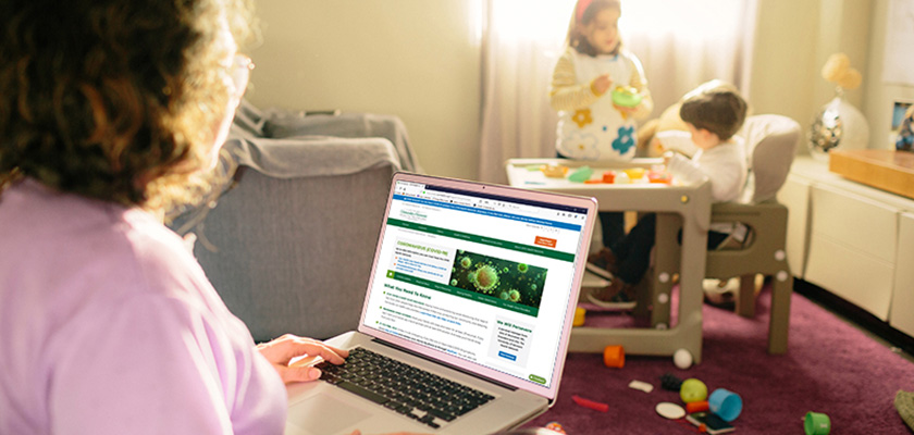 Parent with laptop watching her children