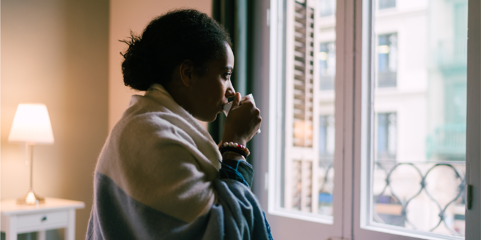 Woman sipping hot drink while looking out window