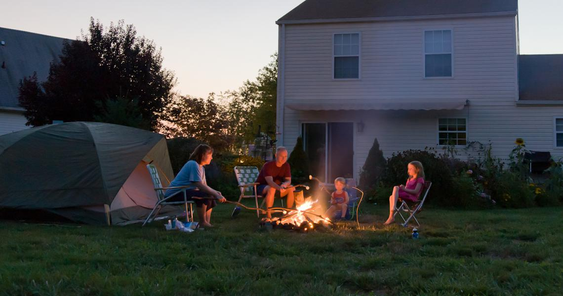 Family sitting around fire pit in their backyard.