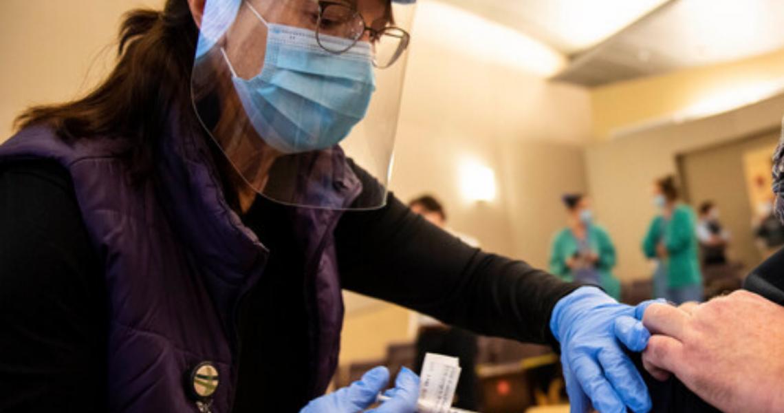 UVMHN employee vaccinating community member