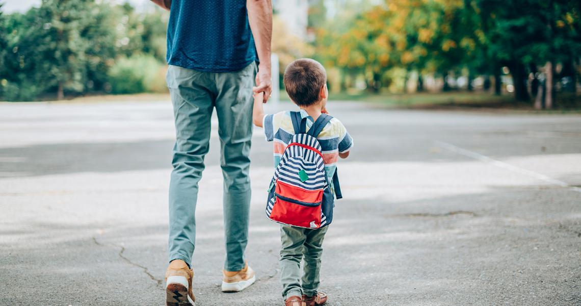 Young boy wearing backpack walking with father to school.