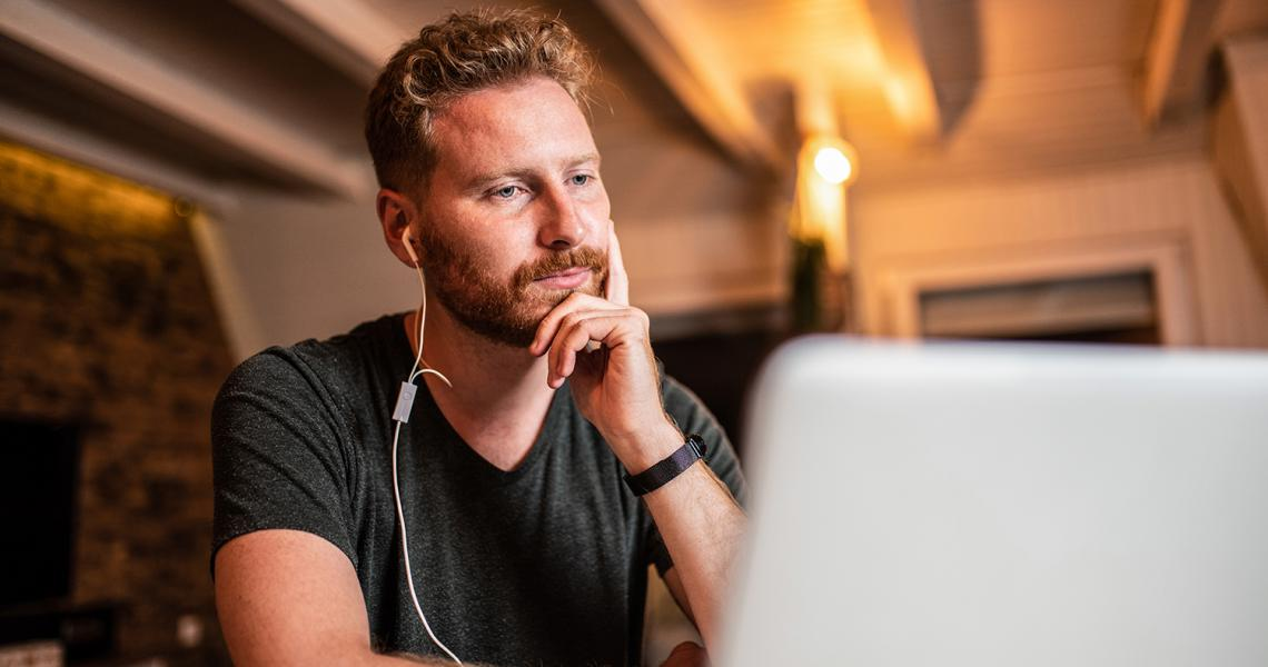 Man sitting at laptop looking bored.