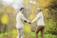 Two seniors holding hands walking on a trail in the fall.