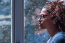 Woman staring out the window in the winter.