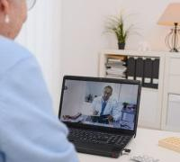 Elderly woman visits with doctor via a laptop