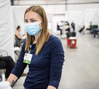 Nurse standing at monitor working at a Essex, VT vaccination Cinic