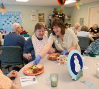 Nurse serving three seniors dinner.