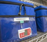 Upclose image of cooler totes holding vaccines. The tote bags are labeled Farigrounds.