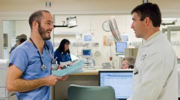 Two emergency medicine physicians talking in the ER.