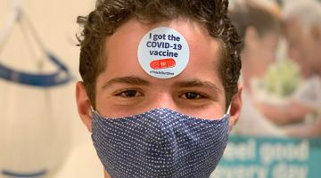 """Portrait of a teenage boy wearing a blue mask. He has a sticker on his forehead """"I got the COVID-19 vaccine."""" ."""