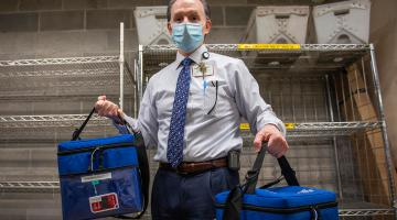 Photo of David Weiss holding two cooler totes of COVID19 vaccines.