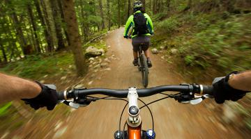 Action shot from bike rider's perspective looking over the handle bars. The mountain biker is riding on a dirt trail in the woods behind another mountain biker.