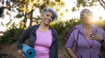 Two women walking outside, exercising.