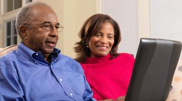 Older couple looking at a laptop while sitting on the couch.