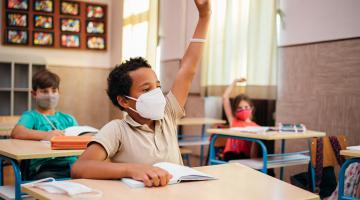African-American schoolboy with protective mask is sitting at a desk in the classroom with raised hand in desire to answer the question.